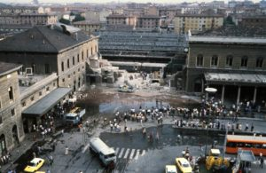 """General view of Bologna Central station and of wagons of the Ancona-Chiasso train pictured on August 02, 1980 in Bologna after a terrorist bombing which killed 85 people and wounded more than 200. At 10:25 am., August 02, a timed improvised explosive device (IED) contained in an unattended suitcase detonated inside an air-conditioned waiting room, which, the month being August (and with air conditioning being uncommon in Italy at the time), was crammed full of people. The IED was made of TNT, T4 and a """"Compound B"""", also known as Composition B. The explosion destroyed most of the main building and hit the Ancona–Chiasso train that was waiting at the first platform. The attack has been attributed to the neo-fascist terrorist organization,"""